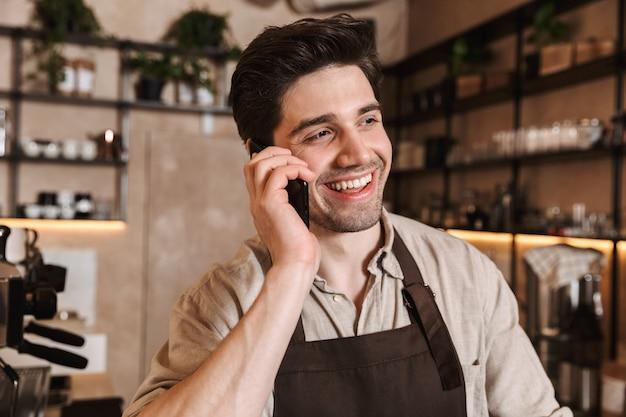 Bild des hübschen glücklichen kaffeemannes, der in der cafébar aufwirft, die drinnen arbeitet und mit dem handy spricht.