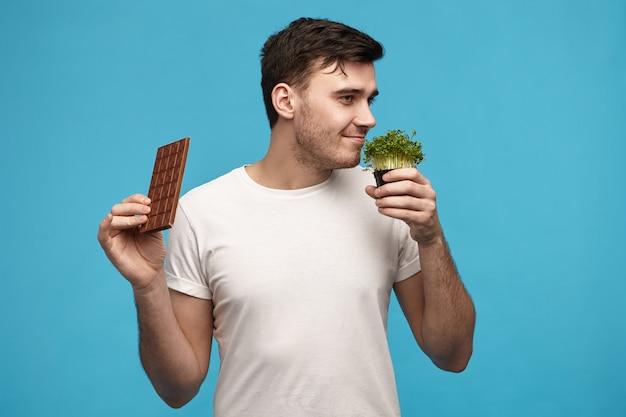 Bild des hübschen jungen brünetten kerls mit der borste, die strenge vegane diät hält