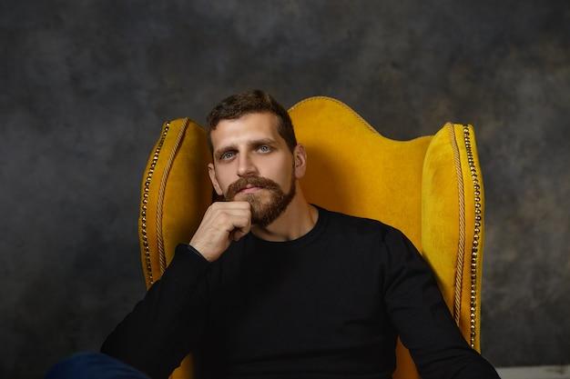 Bild des hübschen jungen kaukasischen bärtigen mannes, der eleganten schwarzen pullover trägt, der im luxuriösen gelben sessel sich entspannt, hand in seinem kinn hält, nachdenklich, nachdenklich nachdenklichen ausdruck habend