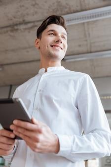 Bild des hübschen jungen mannes, der im weißen hemd unter verwendung des tablet-computers gekleidet wird. coworking. sieh zur seite.