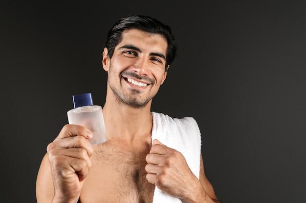Bild des hübschen jungen mannes, der isoliertes halten des toilettenwassers aufwirft.