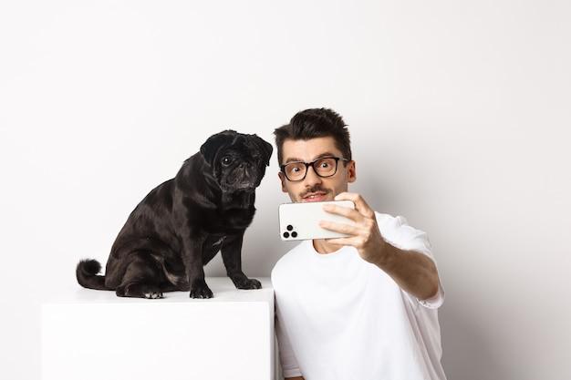 Bild des hübschen jungen mannes, der selfie mit niedlichem schwarzen hund auf smartphone nimmt und mit mops über weiß aufwirft