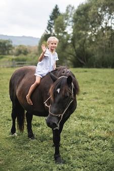 Bild des hübschen kleinen blonden mädchens, das schönes pferd im sommerfeld reitet