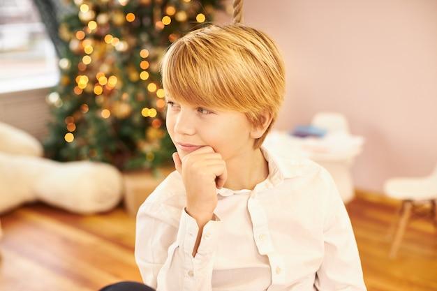 Bild des hübschen teenagers im weißen hemd mit nachdenklichem nachdenklichem blick, kinn berührend, denkend, wo mutter neujahrsgeschenke versteckte, im wohnzimmer mit weihnachtsbaum posierend