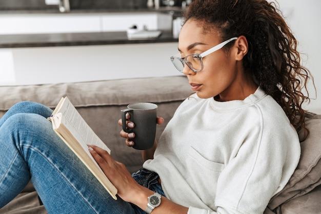 Bild des intelligenten afroamerikanermädchens, das buch liest und tee trinkt, während auf sofa in der hellen wohnung sitzt