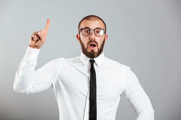 Bild des intelligenten kaukasischen mannes im weißen hemd und in den brillen, die finger nach oben auf kopienraum zeigen oder gestikulieren haben idee, lokalisiert über graue wand