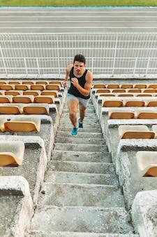 Bild des jungen athletischen mannes, der heraus durch leiter am stadion läuft
