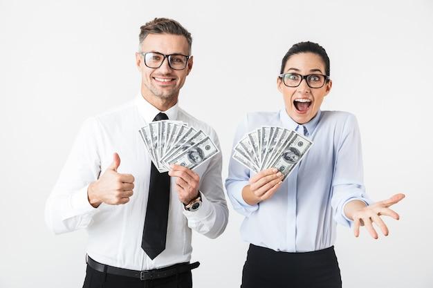 Bild des jungen aufgeregten geschäftskollegenpaares lokalisiert über weißer wand, die geld hält.