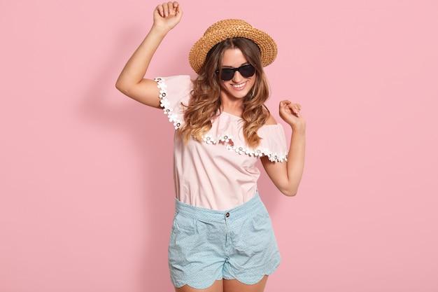 Bild des jungen dunkelhaarigen mädchens mit zufriedenem gesichtsausdruck, der auf rose tanzt, hört lieblingslied. studioaufnahme eines glamourösen weiblichen models in trendigen shorts, bluse, hut und sonnenbrille