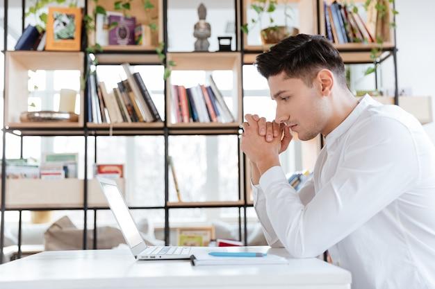 Bild des jungen ernsten mannes im weißen hemd mit laptop-computer gekleidet. coworking. computer betrachten.