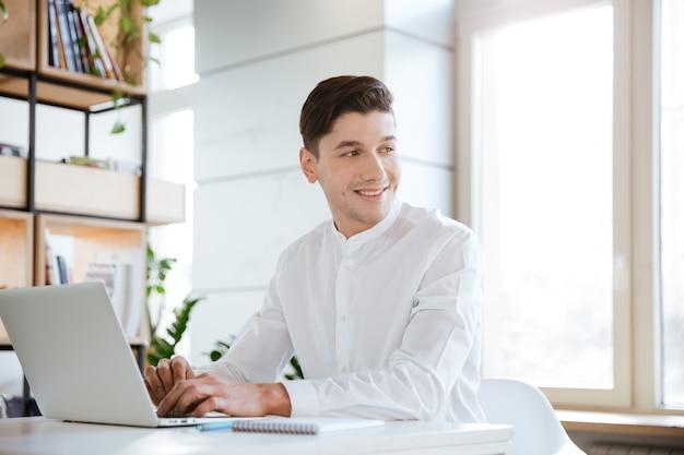 Bild des jungen fröhlichen mannes im weißen hemd mit laptop-computer gekleidet. coworking. beiseite schauen.