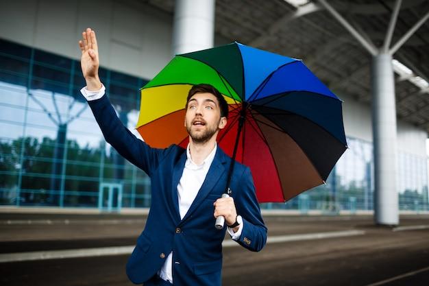 Bild des jungen geschäftsmannes, der bunten regenschirm hält auto am bahnhof hält