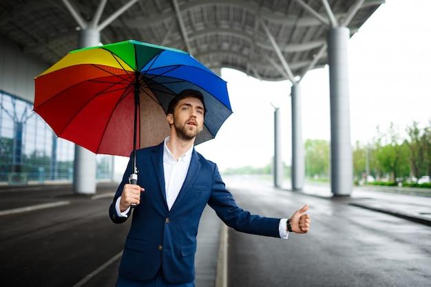 Bild des jungen geschäftsmannes, der bunten regenschirm hält auto am terminal hält