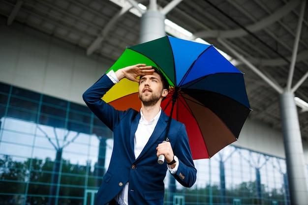 Bild des jungen geschäftsmannes, der bunten regenschirm hält, der auto am bahnhof sucht