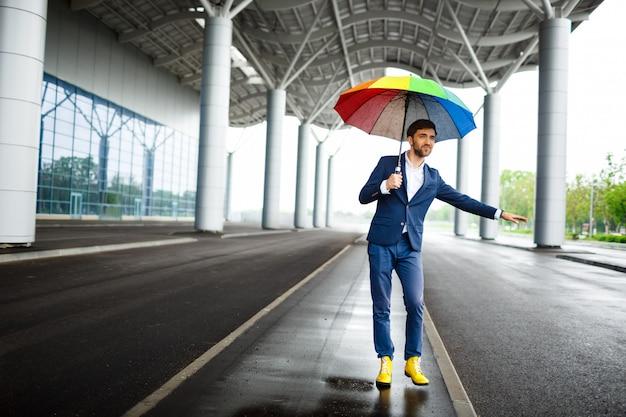 Bild des jungen geschäftsmannes, der bunten regenschirm hält, der das auto am flughafen fängt