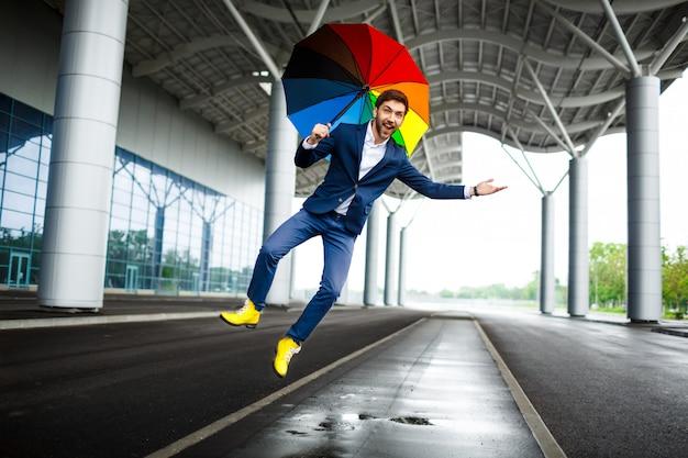 Bild des jungen geschäftsmannes, der bunten regenschirm springt und spaß am bahnhof hat