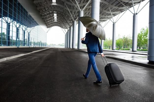 Bild des jungen geschäftsmannes, der koffer und regenschirm am regnerischen terminal hält