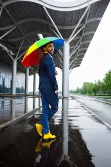 Bild des jungen geschäftsmannes in den gelben schuhen, die bunten regenschirm in der regnerischen straße halten
