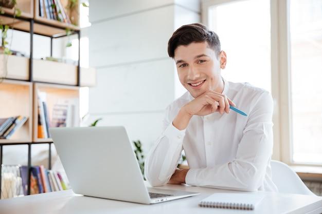 Bild des jungen glücklichen mannes, der im weißen hemd unter verwendung der laptop-computer gekleidet wird. coworking. blick in die kamera.