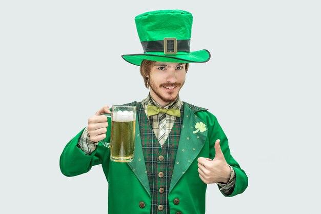 Bild des jungen glücklichen mannes in der grünen st- patrickklage, die becher bier und lächeln hält. er hält einen großen daumen hoch. isoliert auf grau.