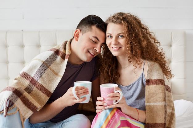 Bild des jungen glücklichen paares, das am morgen kaffee oder tee im bett trinkt, unter warmem plaid sitzt und wochenende genießt