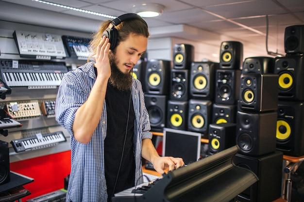 Bild des jungen hipsters, der auf e-piano spielt. er hält eine hand am kopfhörer. er ist mit soundlautsprechern umgeben.