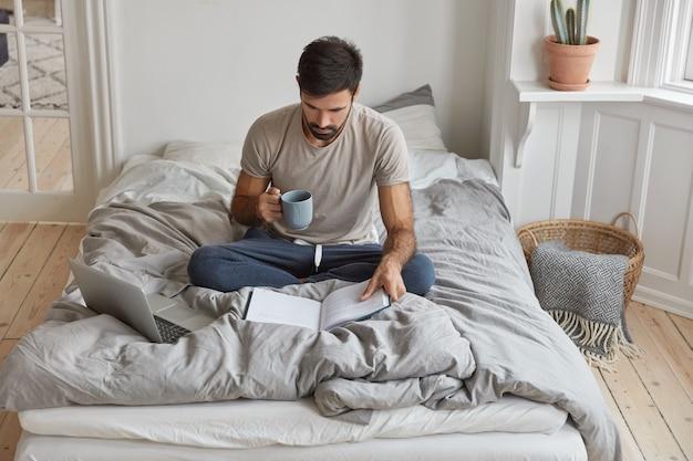Bild des jungen kaukasischen mannes hat morgenkaffee, sitzt gekreuzte beine auf bett