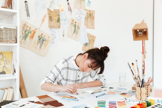 Bild des jungen konzentrierten frauenmodeillustrators
