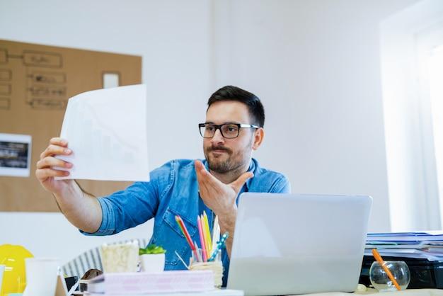 Bild des jungen kreativen ingenieurs, der in seinem büro sitzt und in einigen projekten schaut.