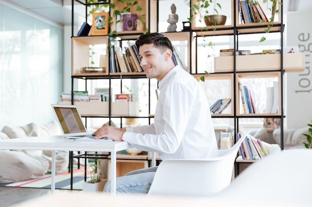Bild des jungen lächelnden mannes, der im weißen hemd unter verwendung der laptop-computer gekleidet wird. coworking. beiseite schauen.