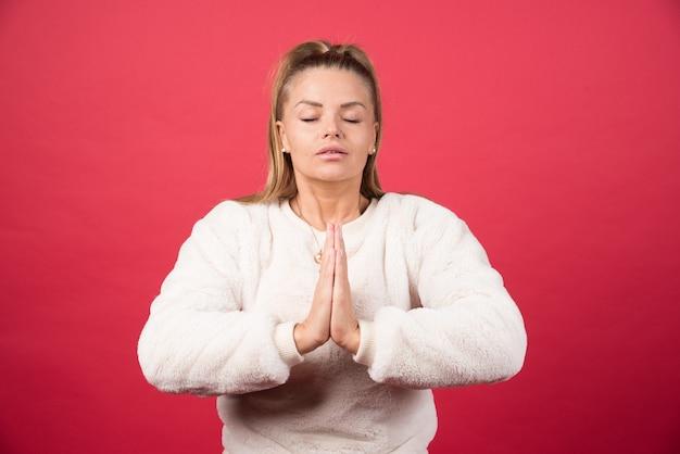 Bild des jungen mädchens, das hände im gebet oder in der meditation zusammensetzt