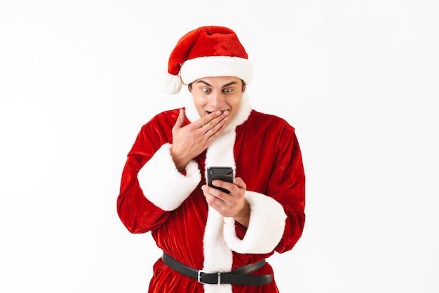 Bild des jungen mannes 30s im weihnachtsmannkostüm, das smartphone hält