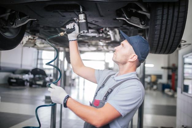 Bild des jungen mannes, der unter auto steht und arbeitet. er sieht auf. guy hält und benutzt bohrer. er arbeitet in weißen handschuhen.