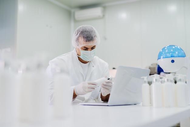 Bild des jungen mannes in der sterilen kleidung, der im hellen labor sitzt und qualität der produkte prüft