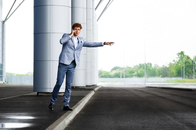Bild des jungen rothaarigen geschäftsmannes, der das auto fängt und am telefon spricht