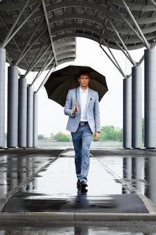 Bild des jungen rothaarigen geschäftsmannes, der regenschirm hält, der auf straße geht