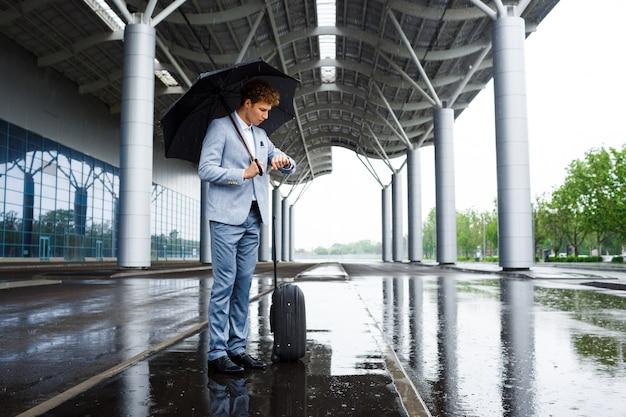 Bild des jungen rothaarigen geschäftsmannes, der schwarzen regenschirm im regen hält und auf uhr schaut