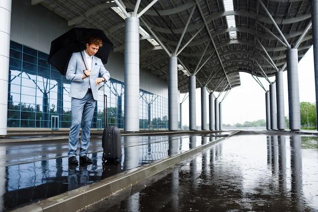 Bild des jungen rothaarigen geschäftsmannes, der schwarzen regenschirm im regen hält und auf wache am bahnhof schaut