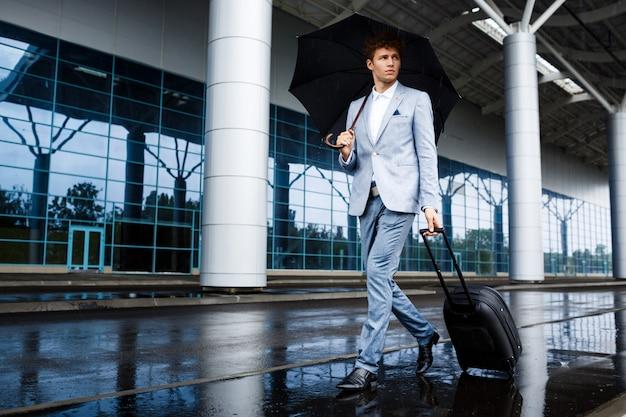 Bild des jungen rothaarigen geschäftsmannes, der schwarzen regenschirm und koffer hält, die im regen am flughafen gehen