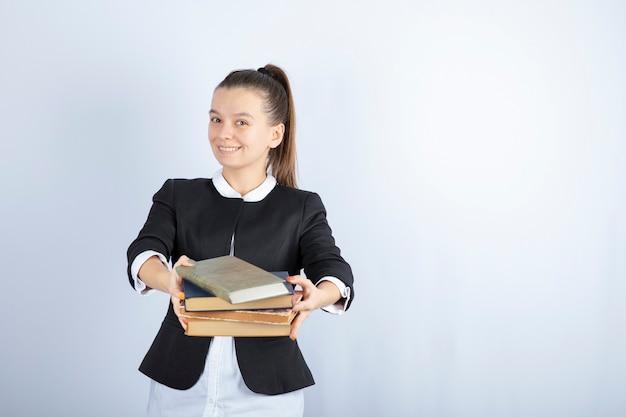 Bild des jungen studenten, der jemandem auf weiß bücher gibt.