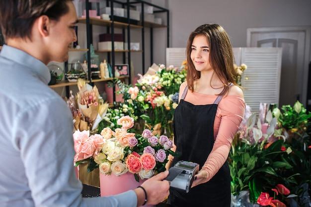 Bild des jungen weiblichen floristen, der geld therminal hält. sie steht vor dem kunden. junger geschäftsmann zahlen für blumen.