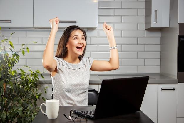Bild des jungen weiblichen unternehmers, der einen laptop beim hände oben anheben und ihren erfolg feiern verwendet