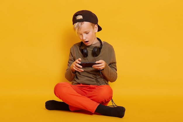 Bild des jungenspiels auf handy. kind sitzt auf dem boden im studio isoliert auf gelber wand und hält handy in händen, spielt sein lieblings-online-spiel, hält die beine gekreuzt.