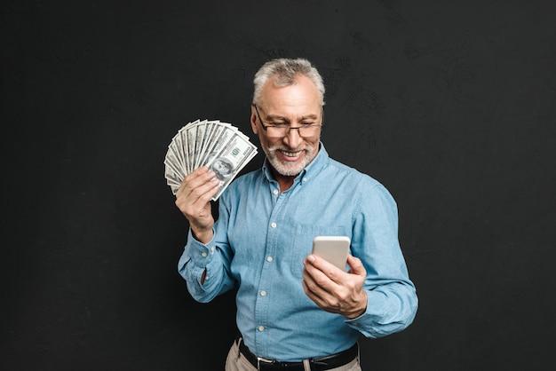 Bild des kaukasischen älteren mannes 70er jahre mit grauem haar, das handy und viel gelddollarwährung hält, lokalisiert über schwarzer wand