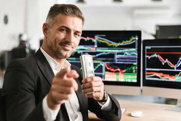 Bild des kaukasischen geschäftsmannes der 30er jahre, der anzug hält packung geld während der arbeit im büro mit grafiken und diagrammen am computer trägt