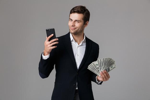 Bild des kaukasischen geschäftsmannes der 30er jahre im anzug, der fan des geldes in den dollar-banknoten und im handy hält, lokalisiert über graue wand