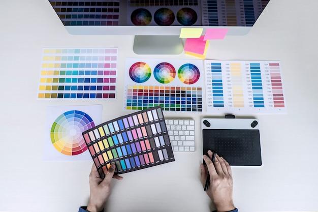 Bild des kreativen grafikdesigners arbeitend an farbauswahl und auf grafiktablett zeichnend