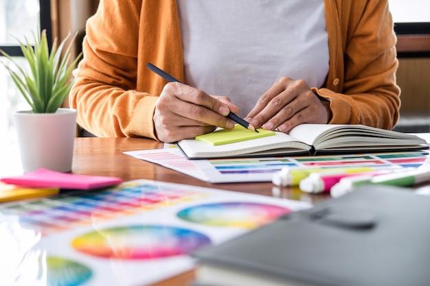 Bild des kreativen grafikdesigners, der an farbauswahl arbeitet und auf grafiktablette zeichnet