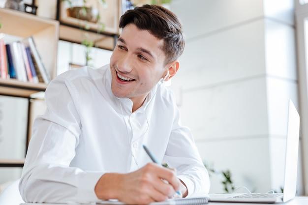 Bild des lachenden mannes in weißem hemd gekleidet mit laptop-computer beim musikhören. coworking. sieh zur seite.