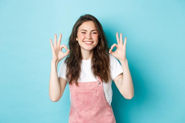 Bild des lächelnden brünetten weiblichen modells sagt ja, zeigt in ordnung zeichen zur zustimmung, stimmt zu oder lobt gute wahl, empfiehlt produkt, steht vor blauem hintergrund.